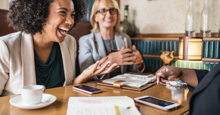 Two women laughing during meeting.