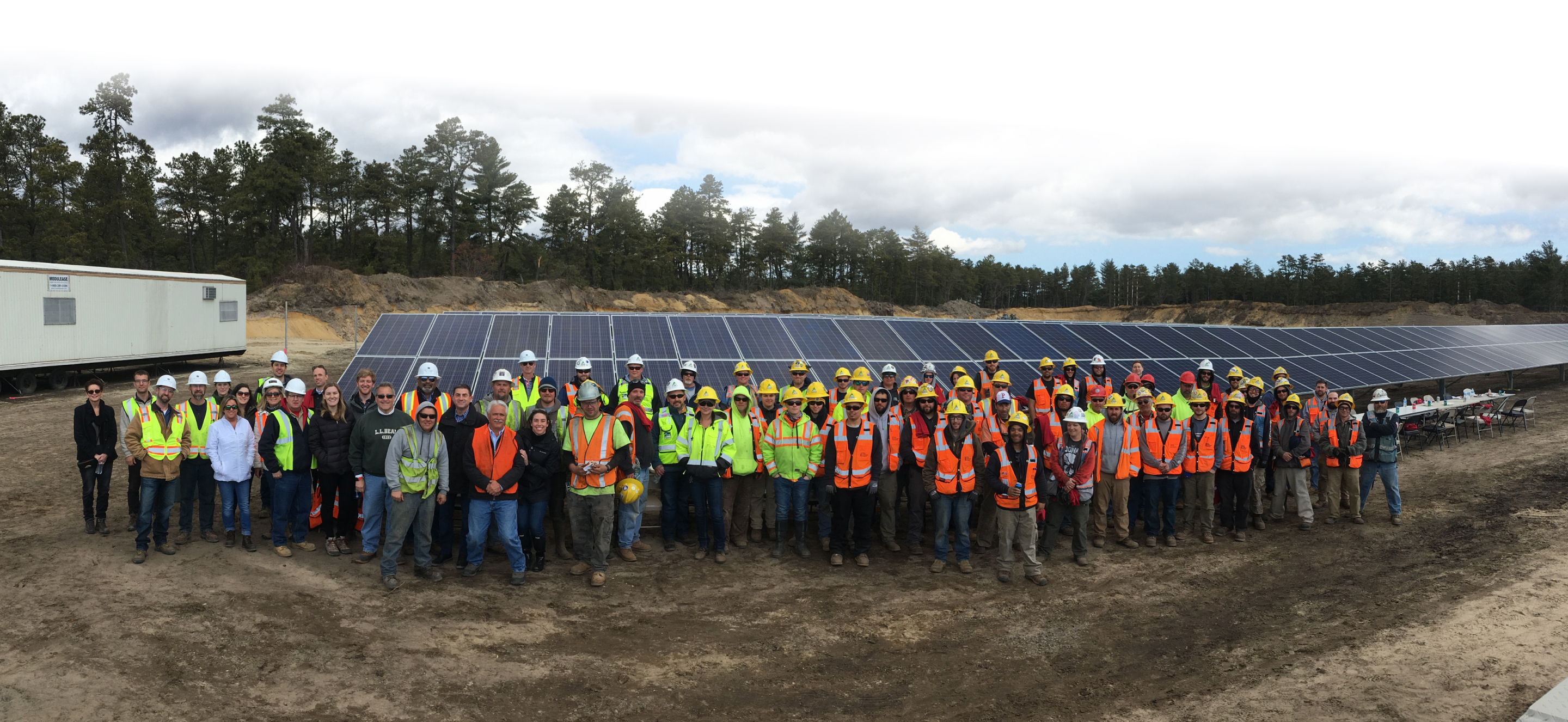 Construction team in front of solar panels.