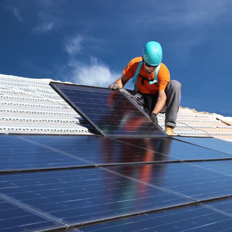 Man installing solar panel on roof.