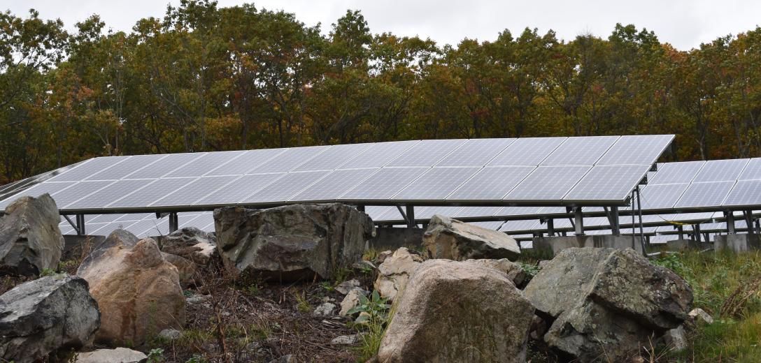Solar panels above rocks.