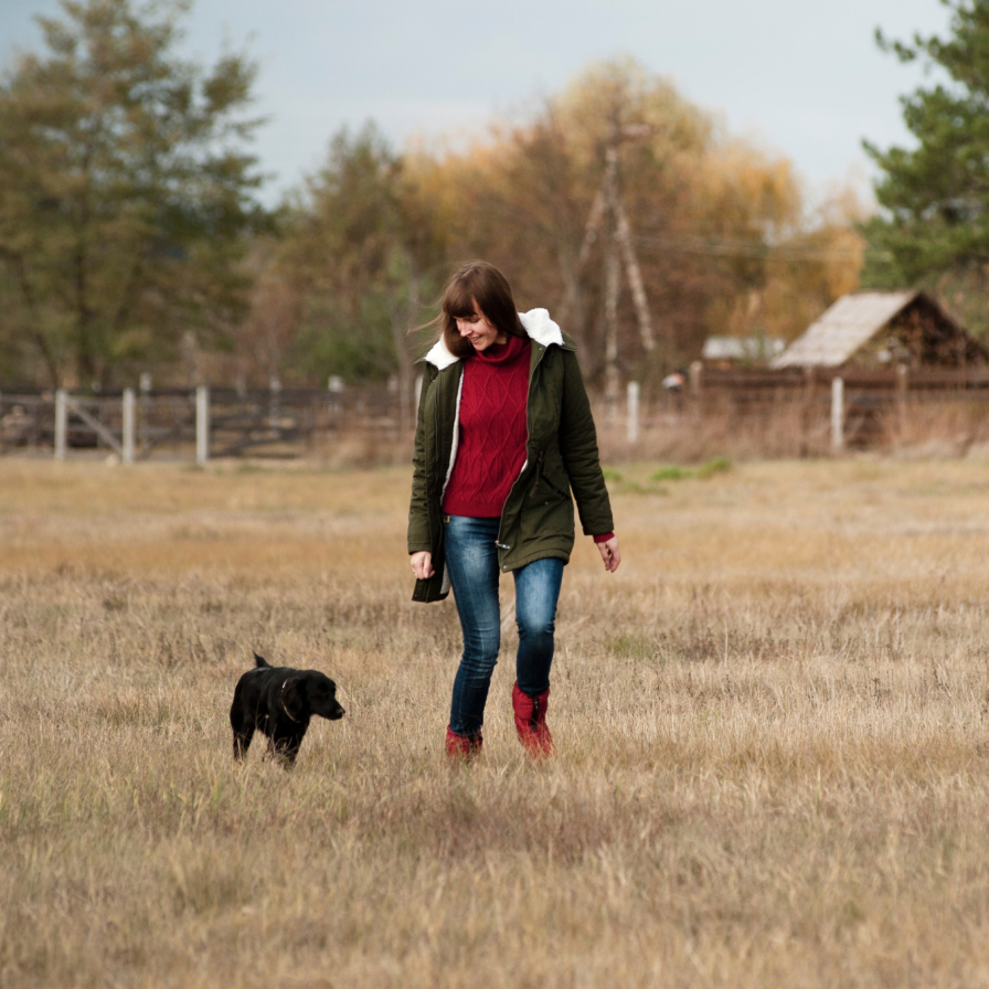 Woman strolling in field with a black dog.