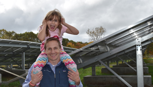 Child sitting on someones shoulders in a solar farm.